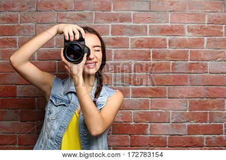 Beautiful young photographer near brick wall