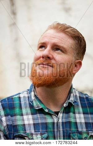 Portrait of red haired man with plaid shirt and long beard