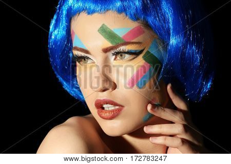 Face of young woman with creative make up and blue hair on black background