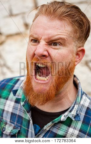 Expressive red haired hipster man with blue plaid shirt expressing a emotion