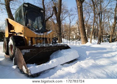 horizontal front view of a small empty tractor with snowplough covered in snow in the park wintertime