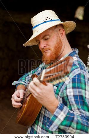 Hipster man with red beard playing the guitar in a rural enviroment