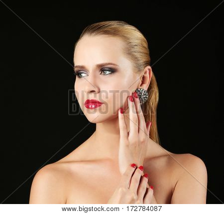 Portrait of beautiful young woman touching face with hand, on black background