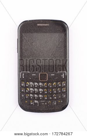 Front view close up of old black smartphone mobile with qwerty keyboard covered in dust and isolated on white background