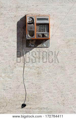 Vertical front view of damaged orange public phone with hanging broken handset against a scratched white wall