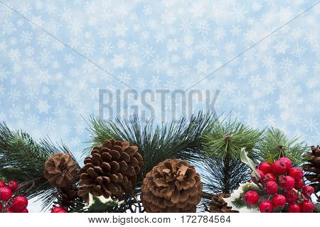 Winter time background Garland with pine cones and red holly berries on snowflake background with copy space for your message