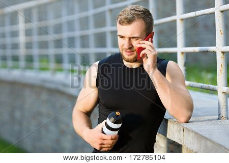 Man standing near stadium with red mobile phone, talking on phone and holding bottle with water. Sportsman with phone leaning with elbow on fence. Outdoors, waist up