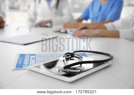 Tablet and stethoscope on table in clinic