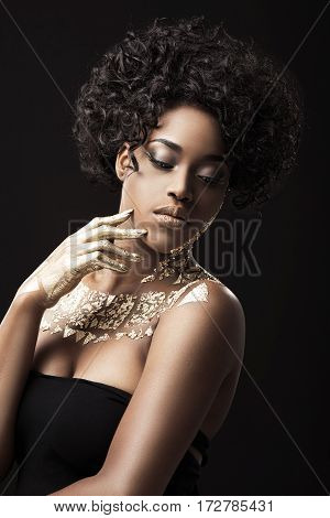 Beautiful Afro-American girl with curly hair in black dress. Make-up, hairdo. Covered with golden patterns. Looking aside and down. Waist up, indoors, studio