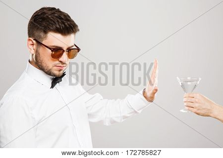 Attractive man with black hair and beard wearing white shirt with bowtie and sunglasses at gray studio background deny to take a glass of alcohol.