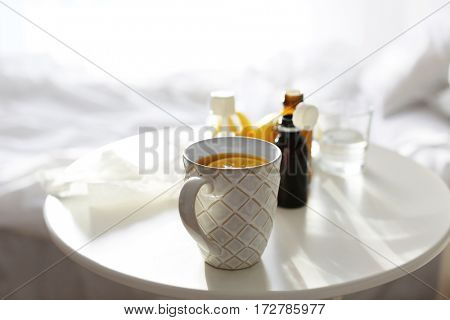 Cup of hot tea and medicines on table at home