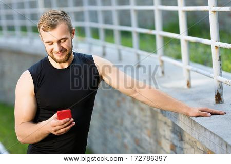 Man standing near stadium with red mobile phone, looking at phone and smiling. Sportsman with phone leaning on fence with one hand. Outdoors, waist up