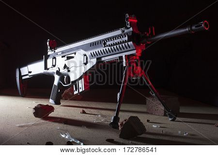 Assault rifle on a dark background with red coming from the right
