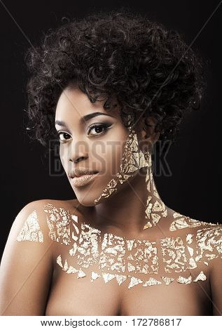Portrait of beautiful Afro-American girl with dark curly hair. Make-up, hairdo. Covered with golden patterns. Looking at camera. Head and shoulders, indoors, studio