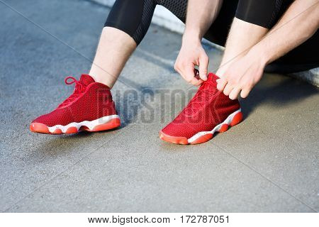 Sport concept. Sportsman sitting and tightening lacings of red sneakers. Without head. Outdoors, only legs, closeup