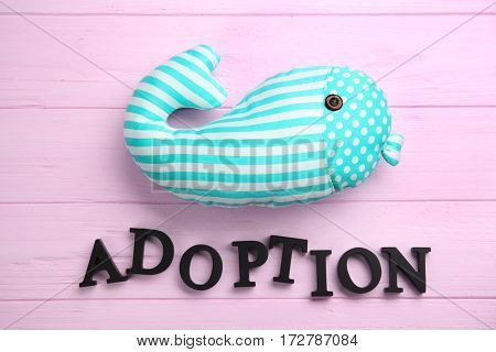 Word ADOPTION and whale toy on color wooden background