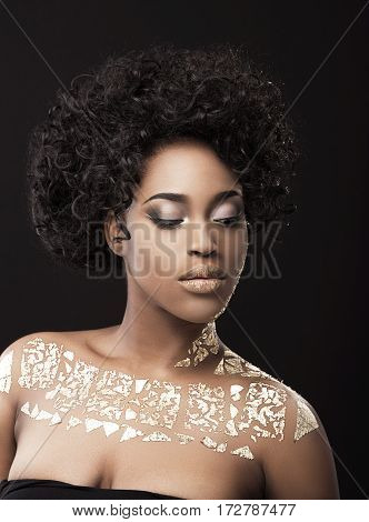 Portrait of beautiful Afro-American girl with dark curly hair. Make-up, hairdo, gold. Covered with golden patterns. Looking down. Head and shoulders, indoors, studio