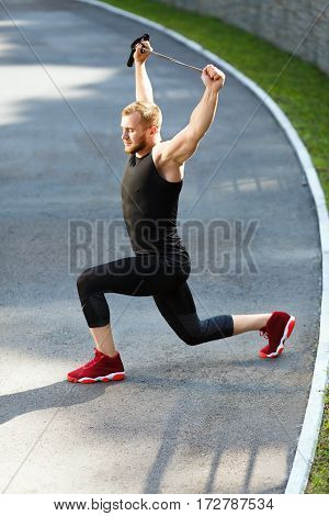 Profile of man training with expander, closed eyes. Muscular sportsman lunging with expander, hands up, leaning on one knee. Sport, outdoors, stadium, full body, vertical