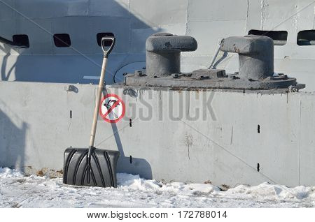Plastic shovel for snow removal on the dock is standing at the curb.