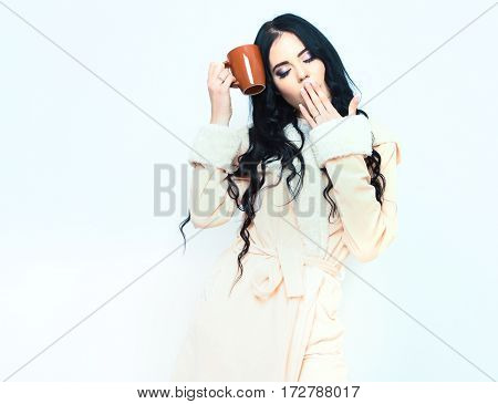 Sexy Yawning Girl In Beige Velour Bathrobe Holding Cup
