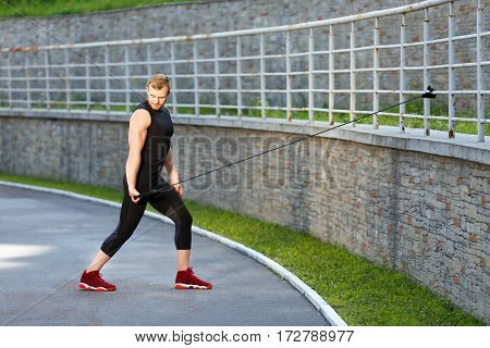 Full body of man training with expander hooked on fence. Muscular sportsman pulling expander to himself with one hand and looking down. Sport, outdoors, stadium