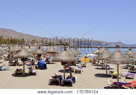 Playa De Las Americas beach Tenerife Canary Islands Spain Europe - June 12 2016: Tourists on the beach enjoying the sun