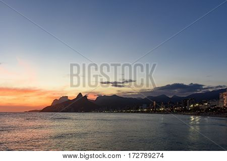 Landscape of the beaches of Arpoador Ipanema and Leblon in Rio de Janeiro during dusk with its lights moon and sky and the hill Two brothers and Gávea stone in the background