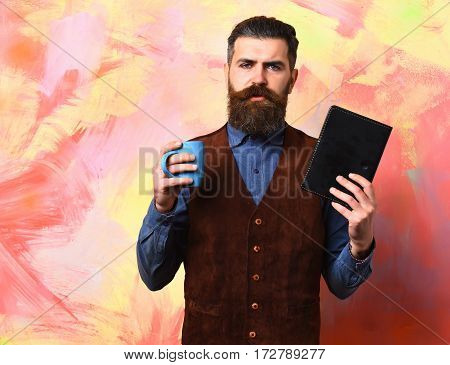 Bearded Brutal Caucasian Hipster With Coffee Cup And Black Notebook