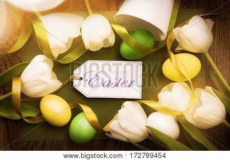 Easter decoration with tulips and greeting label in sunlight