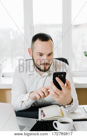 bearded businessman in white shirt looking at the phone