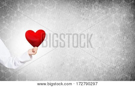 Hand of woman doctor against gray background holding red heart