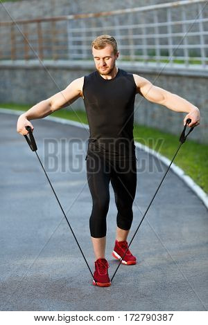 Man training with expander. Muscular sportsman standing on expander with one leg and holding it with both arms, pulling it to himself. Full body, outdoors, stadium