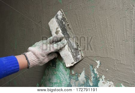 female's hand with a trowel plaster wall outdoor closeup