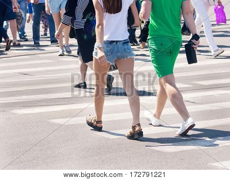 pedestrians walk on a pedestrian crossing on sunny summer day