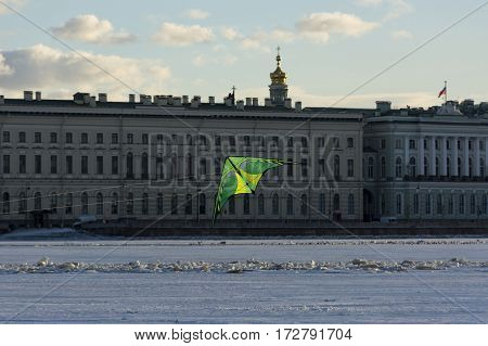 green kite flying over the river Neva opposite the Palace embankment and the Hermitage buildings city snow winter