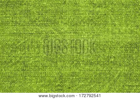 Homespun hemp cloth. Close-up of texture fabric cloth textile background. Homespun hemp fabric material. Homespun hemp canvas. Natural authentic cloth. Lime green color