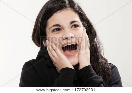 Very surprised girl with black clothing, portrait in studio