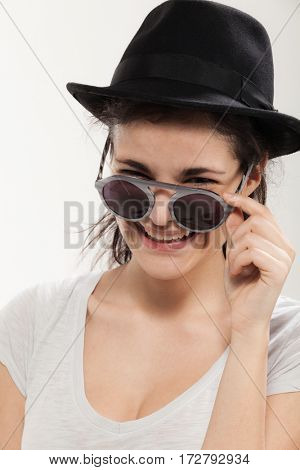 Girl with a black hat and stylish glasses, studio portrait