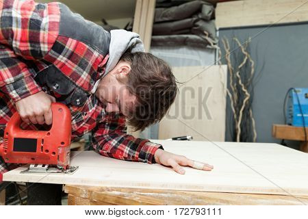 Young carpenter in his workshop using an electric saw to cut a wooden plank