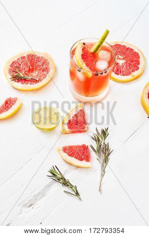 Refreshing homemade grapefruit and rosemary cocktail on white wooden table.
