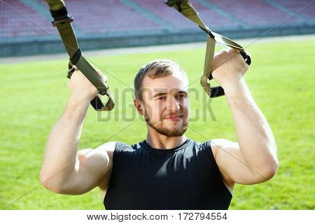 Man training with training loop. Muscular sportsman holding training loop with both arms, looking aside and smiling. Waist up, outdoors, stadium