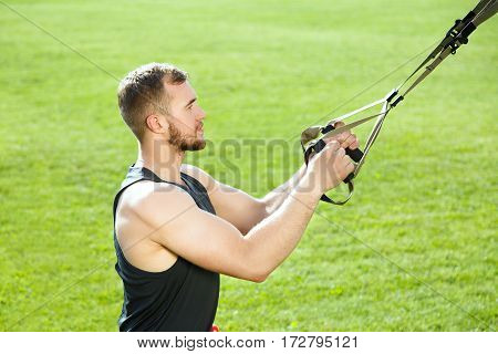 Profile of man training with training loop. Muscular sportsman holding training loop with both arms. Waist up, outdoors, green grass on background