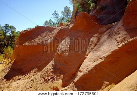 Oragne ochre picturesque hills. Roussillon village, Luberon, Provence France. Preserve natural dye production - ocher.
