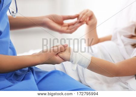 Closeup of doctor holding girl's hands in hospital