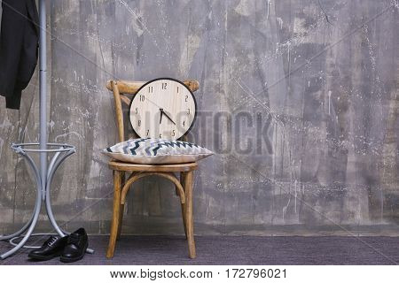 Wooden chair with pillow and clock on grey wall background