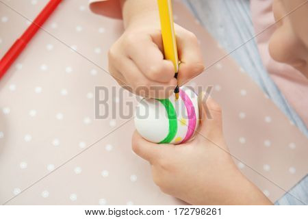 Little girl decorating Easter egg