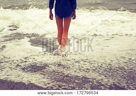 Slender legs.Girl and the sea.Photo toned in retro style.