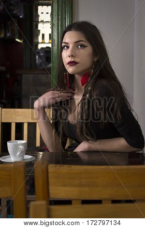 Girl sitting at the table, cup is in front of her.
