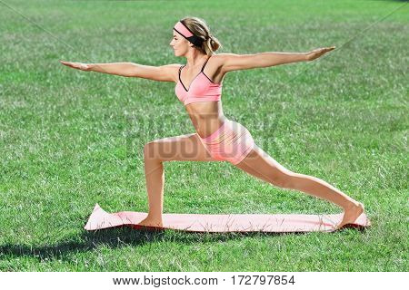 Girl in rose training suit doing yoga asana in park. Profile of young woman standing on mat, one leg bent, hands outstretched, virabhadrasana. Outdoors, nature, full body, profile