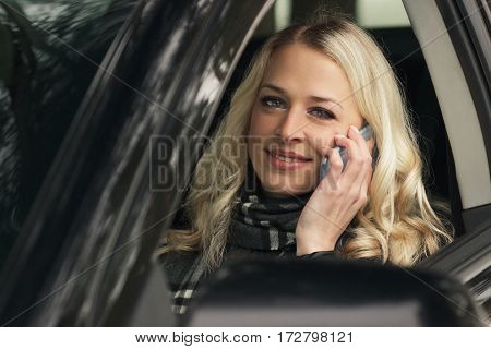 Young Woman Sitting In The Car And Talking By The Phone